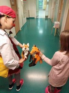 Klovni ja lapsi sairaalan käytävällä, selin katsojaan. Molemmilla on kädessä kettulelu.