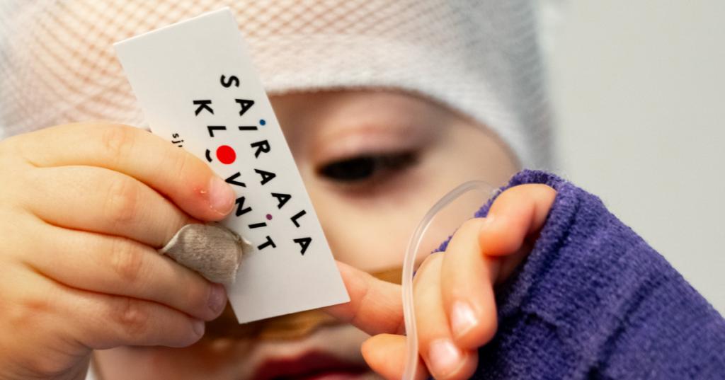 """Pieni lapsi pitää käsissään korttia, jossa lukee """"Sairaalaklovnit"""". Lapsen pää ja toinen käsi on kääritty siteisiin."""